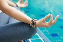 La donna che medita con il polso borda in una posizione di yoga del loto immagine stock libera da diritti
