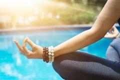 La donna che medita con il polso borda in una posizione di yoga del loto al bl immagini stock