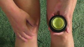 La donna che mette la crema dell'unguento sul Male ha ferito il ginocchio stock footage