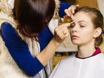 La donna che ottiene gli occhi compone fatto dall'artista Fotografia Stock