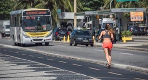 La donna che pareggia sul percorso corrente fronte mare davanti alla strada di traffico alla spiaggia di Copacabana immagini stock