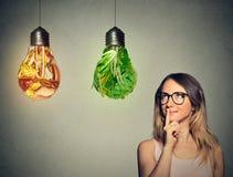 La donna che pensa cercando gli alimenti industriali e le verdure verdi ha modellato come lampadina Fotografia Stock Libera da Diritti