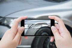 La donna che per mezzo dello smartphone mobile prende l'incidente di incidente stradale della foto Fotografie Stock