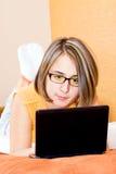 La donna che per mezzo di un computer portatile si è distesa nella sua base immagine stock