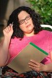La donna che porta i vetri si siede e pensa la strategia Immagini Stock