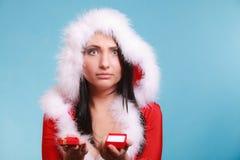 La donna che porta il costume del Babbo Natale tiene il contenitore di regalo sul blu Fotografia Stock Libera da Diritti