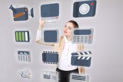 La donna che preme il tipo alta tecnologia di multimedia moderne si abbottona su un fondo virtuale Immagine Stock