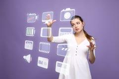 La donna che preme il tipo alta tecnologia di multimedia moderne si abbottona su un fondo virtuale Fotografie Stock Libere da Diritti