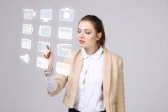 La donna che preme il tipo alta tecnologia di multimedia moderne si abbottona su un fondo virtuale Fotografia Stock