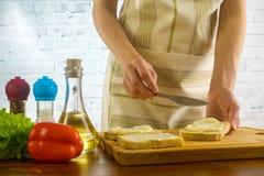 La donna che preparano i panini e le diffusioni imburrano sul pane Fotografia Stock