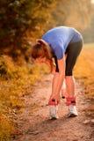 La donna che regola la sua caviglia pesa i polsini Immagini Stock