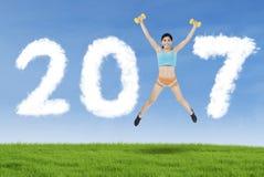 La donna che salta con il numero 2017 nel prato Immagini Stock
