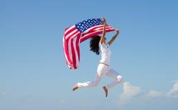 La donna che salta con la bandiera americana Fotografia Stock