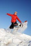 La donna che salta con lo snowboard fotografie stock