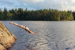 La donna che salta da una roccia fotografia stock