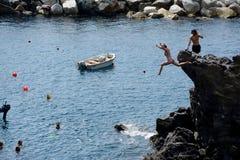 La donna che salta dall'alta roccia al mare nella città di Manarola Immagini Stock Libere da Diritti