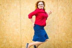 La donna che salta davanti al recinto dai pannelli di legno del mdf - l'umore divertente immagini stock