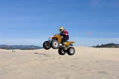La donna che salta il suo ATV nelle dune Fotografie Stock Libere da Diritti