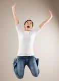 La donna che salta nell'incoraggiare del mid-air fotografia stock