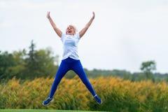 La donna che salta per la gioia con le armi e la diffusione delle gambe fotografie stock