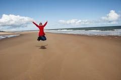La donna che salta per la gioia Immagini Stock