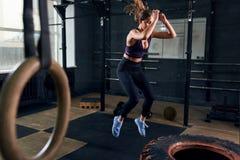 La donna che salta sulla gomma enorme nella palestra di CrossFit Fotografie Stock Libere da Diritti