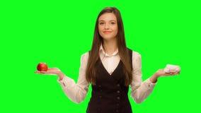 La donna che sceglie di mangiare l'hamburger invece della mela seleziona la mela video d archivio