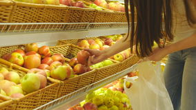 La donna che seleziona le mele rosse fresche in drogheria produce il dipartimento e metterlo nel sacchetto di plastica La giovane video d archivio