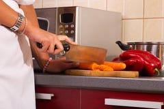La donna che si leva in piedi nella cucina e prepara l'alimento Fotografia Stock Libera da Diritti