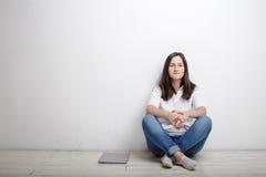 La donna che si siede contro la parete sul pavimento è taccuino Immagini Stock