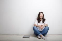 La donna che si siede contro la parete sul pavimento è taccuino Immagine Stock Libera da Diritti