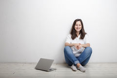 La donna che si siede contro la parete sul pavimento è taccuino Immagini Stock Libere da Diritti