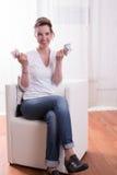 La donna che si siede in poltrona e che conta i soldi è felice Immagine Stock