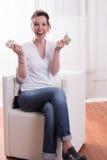 La donna che si siede in poltrona e che conta i soldi è felice Immagini Stock Libere da Diritti