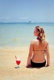 La donna che si siede sopra insabbia con il cocktail Fotografia Stock Libera da Diritti