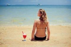 La donna che si siede sopra insabbia con il cocktail Fotografia Stock