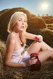 La donna che si siede sul fieno e mangia i lamponi Fotografie Stock Libere da Diritti