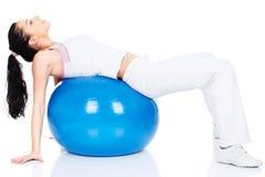 La donna che si trova sopra appoggia sulla sfera dei pilates immagine stock