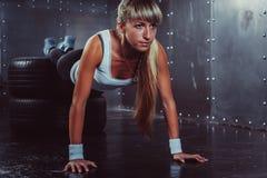 La donna che sportiva dell'atleta fare spinge aumenta sulla gomma Immagini Stock Libere da Diritti