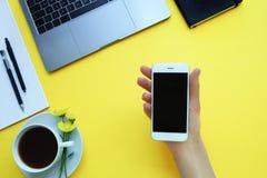 La donna che tiene un telefono all'ufficio della tavola Fondo giallo immagini stock