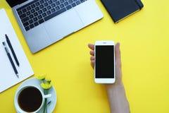 La donna che tiene un telefono all'ufficio della tavola Fondo giallo con il computer portatile, la nota ed il caffè fotografie stock libere da diritti