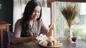 La donna che versa un miele fresco sulla cima del pane tostato del miele prima mangia video d archivio