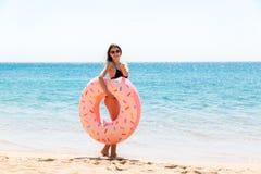 La donna chiama per nuotare nel mare ed ondeggia la sua mano Ragazza che si rilassa con la ciambella sulla spiaggia e che gioca c fotografie stock