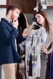 La donna chiede al suo ragazzo di presentare il suo vestito Fotografie Stock Libere da Diritti