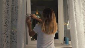 La donna chiude la finestra e le tende prima di andare a dormire a casa video d archivio
