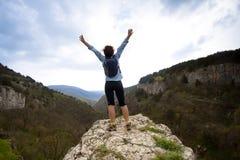 La donna in cima alla montagna raggiunge per il sole Immagine Stock