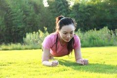 La donna cinese asiatica di forma fisica fa l'esercizio della plancia Fotografia Stock