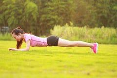 La donna cinese asiatica di forma fisica fa l'esercizio della plancia Immagine Stock Libera da Diritti