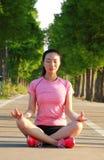La donna cinese asiatica di forma fisica fa l'yoga Immagini Stock