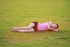 La donna cinese asiatica felice ha un resto su erba Fotografie Stock Libere da Diritti